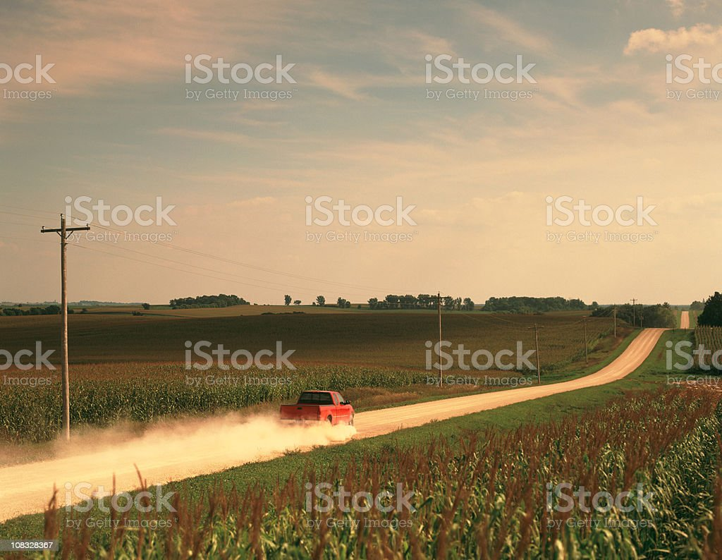 Red Pick Up Truck Traveling Down a Dusty Midwest Road. stock photo