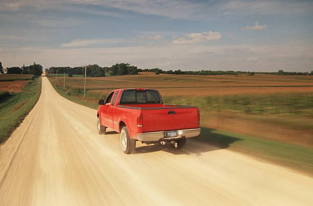 red pick up truck traveling down a dusty midwest road. - pikap stok fotoğraflar ve resimler