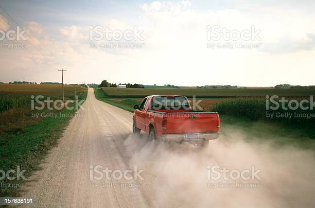 Red pick up truck traveling down dusty rural road.
