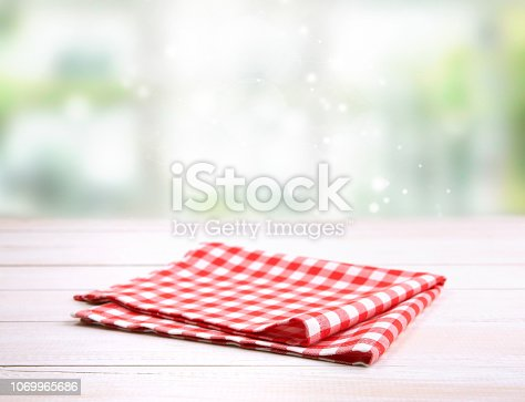 Checkered folded gingham red picnic cloth on wooden table empty space backdrop.Kitchen napkin.