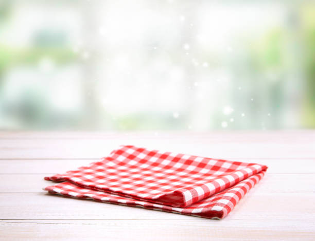 Red picnic gingham folded cloth on table. Checkered folded gingham red picnic cloth on wooden table empty space backdrop.Kitchen napkin. napkin stock pictures, royalty-free photos & images