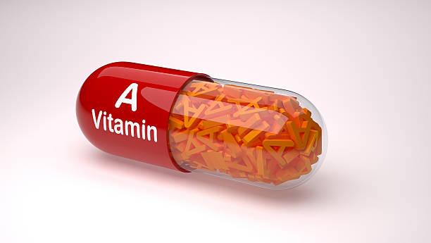 red pill or capsule filled with vitamin a. - vitamina a fotografías e imágenes de stock