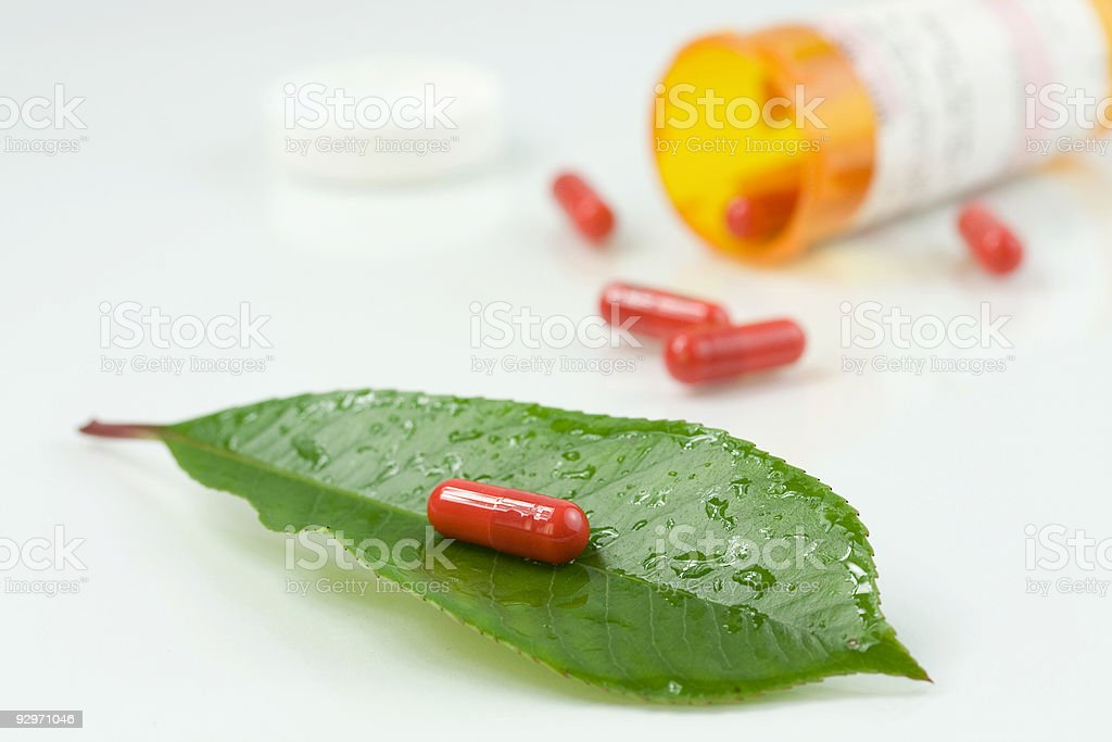 Red pill over a green leaf royalty-free stock photo