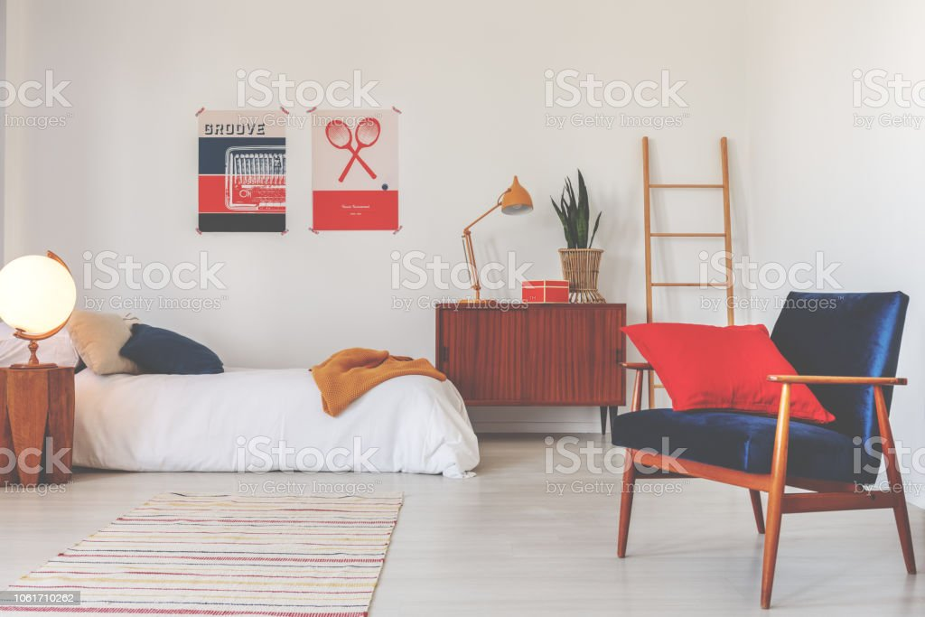 Red pillow on blue armchair in white bedroom interior with wooden cabinet next to bed. Real photo stock photo