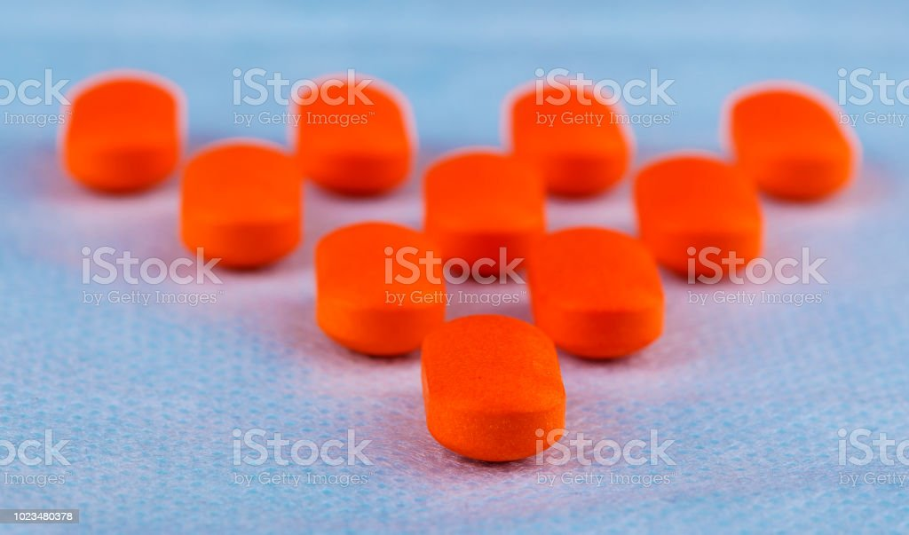 Red pills or capsules in blue background stock photo
