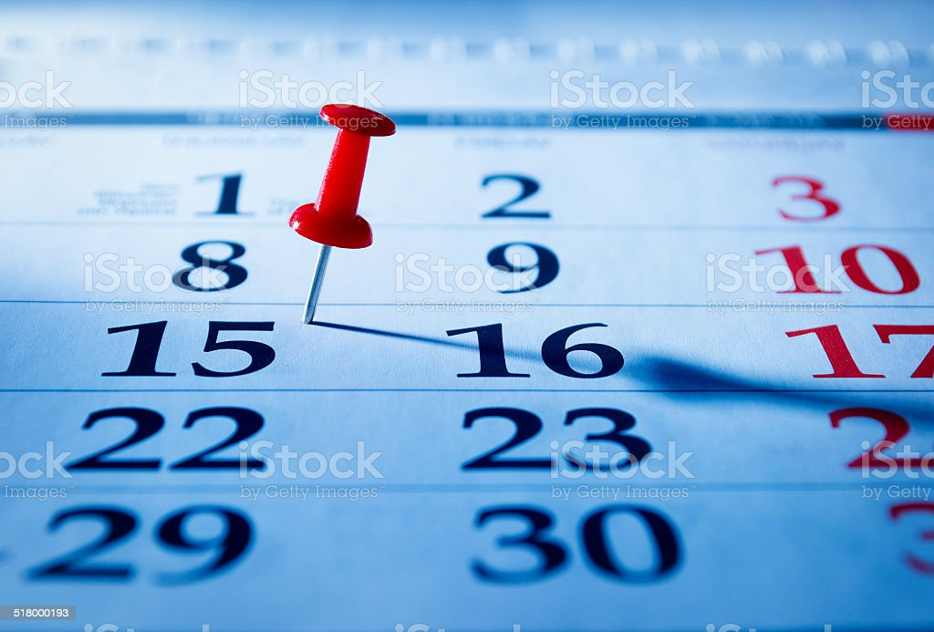 Red pin marking the 15th on a calendar stock photo