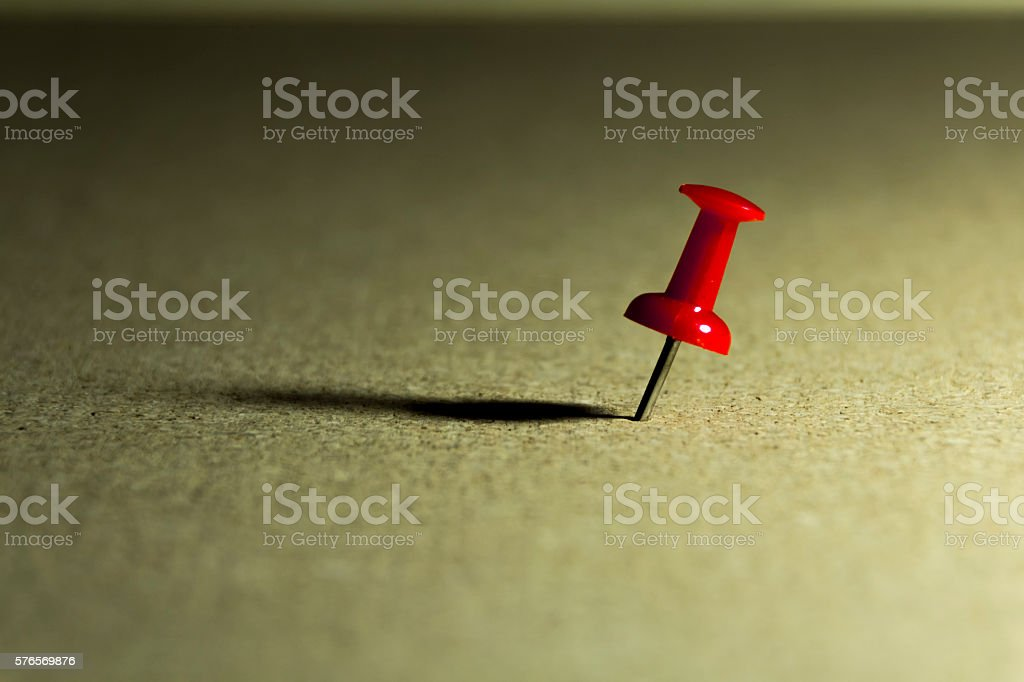 Red pin on corkboard stock photo