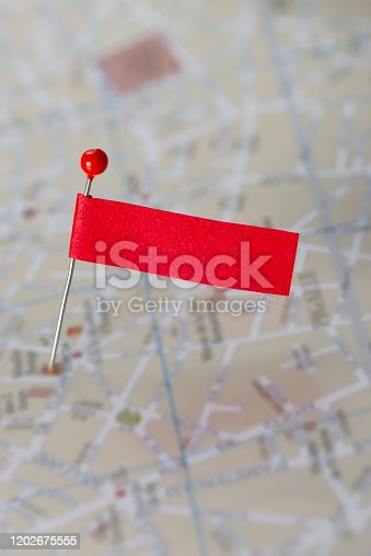 Red pin and blank flag on city map.