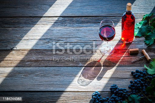 Red pink wine concept bottle and wine glass corkscrew on wooden rustic table board