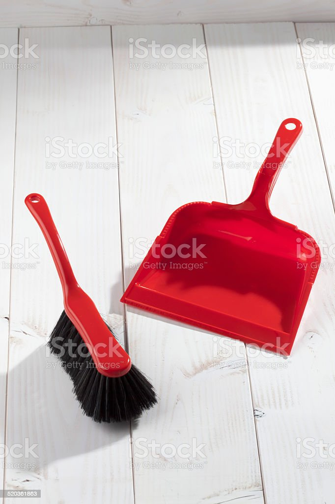 Red plastic brush and dustpan on white wooden background stock photo