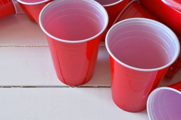 Red Plastic Drinking Cups A close up image of empty red plastic drinking cups on a white picnic table. disposable cup stock pictures, royalty-free photos & images