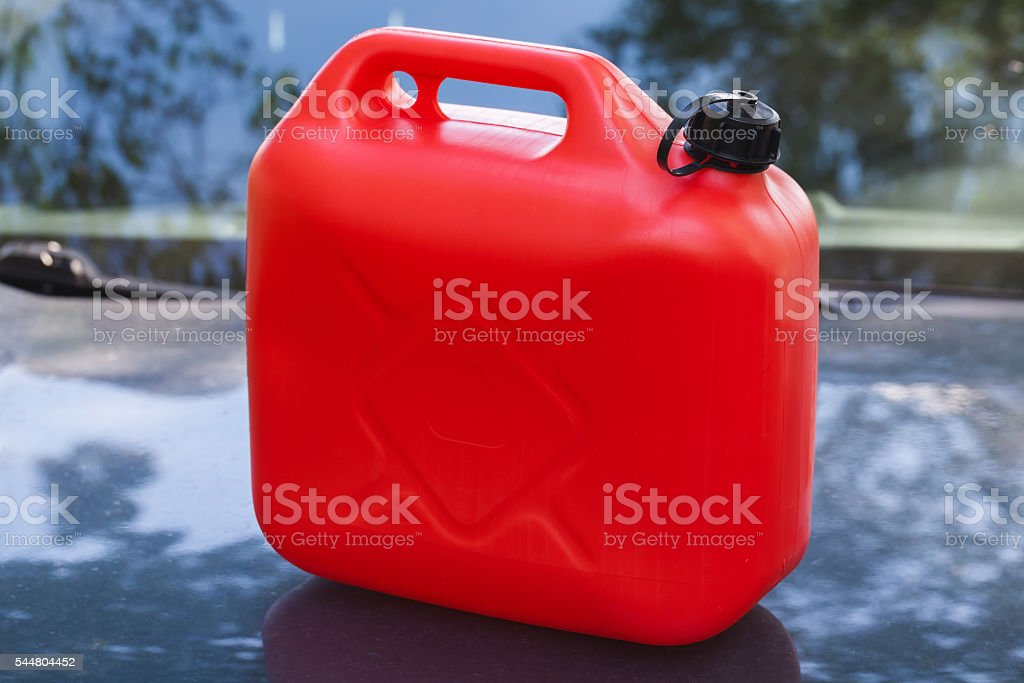 Red plastic jerry can stands on car hood stock photo