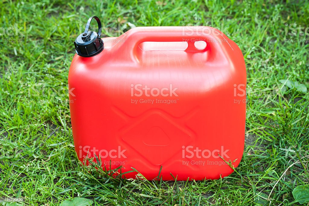Red plastic jerrycan stands on green grass stock photo