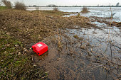 Striking red plastic jerrycan washed up during the high water level in the Dutch rivers.