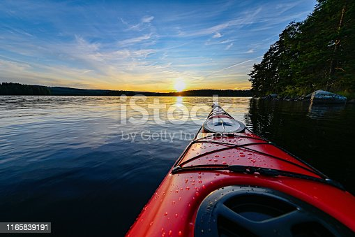red plastic kayak on calm water in the sunset Filipstad july 31 2019