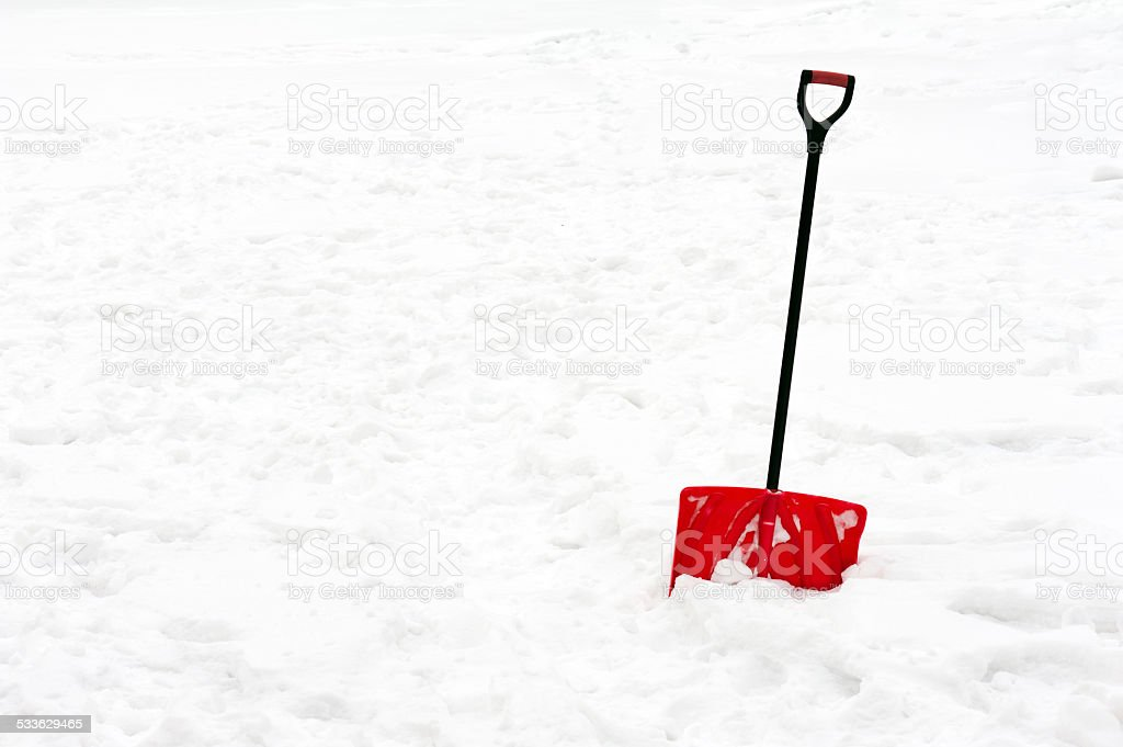 Red plastic shovel with black handle stuck in fluffy snow. stock photo