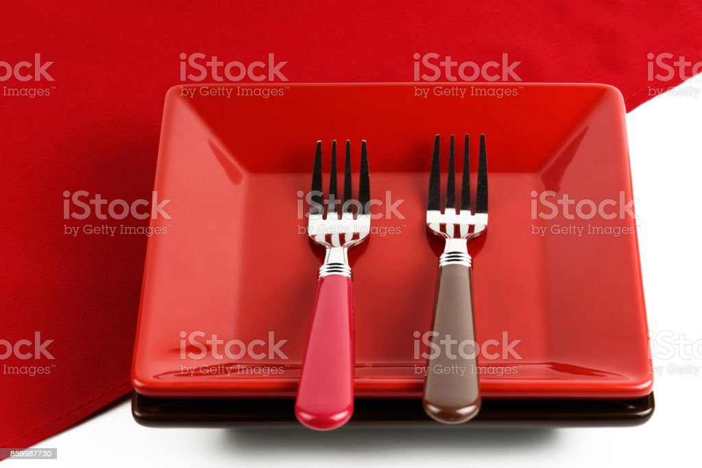 Red plate and two forks on a red napkin. stock photo