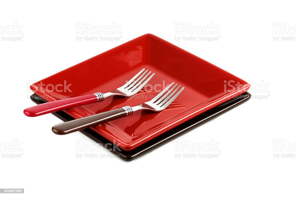 Red plate and two forks on a white background. stock photo