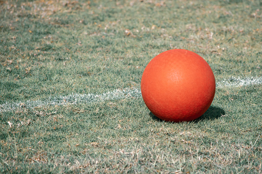 A red playground ball sits next to the white line on a green grass field. Aged or antique look.