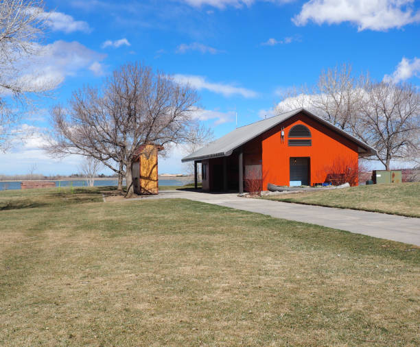 Red pole barn by a lake and grass area stock photo