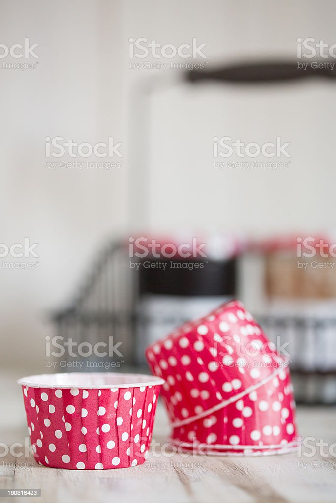 Red polka dot cupcake liners with jam behind stock photo