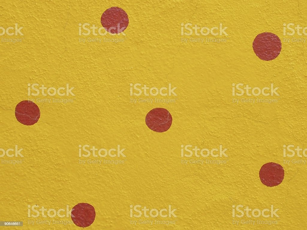Red Polka Dots on Yellow Cement Wall stock photo