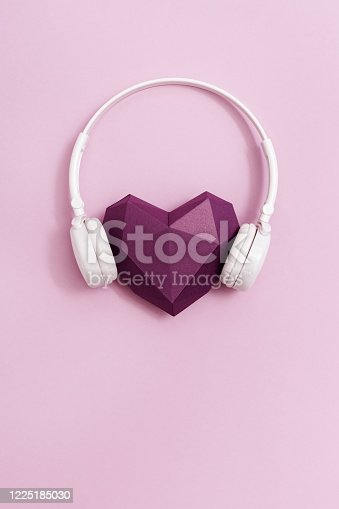 Red polygonal paper heart shape purple colored in white headphones. Music concept. Dj Headset. Minimal style.