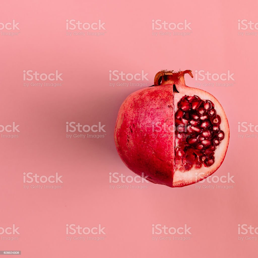 Red pomegranate fruit on pastel pink background. Minimal flat la stock photo