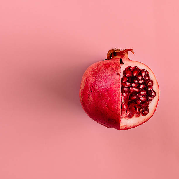 red pomegranate fruit on pastel pink background. minimal flat la - granada fruta tropical fotografías e imágenes de stock