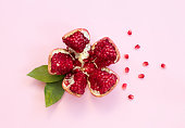 Red pomegranate fruit on pink background. Minimal flat lay concept.