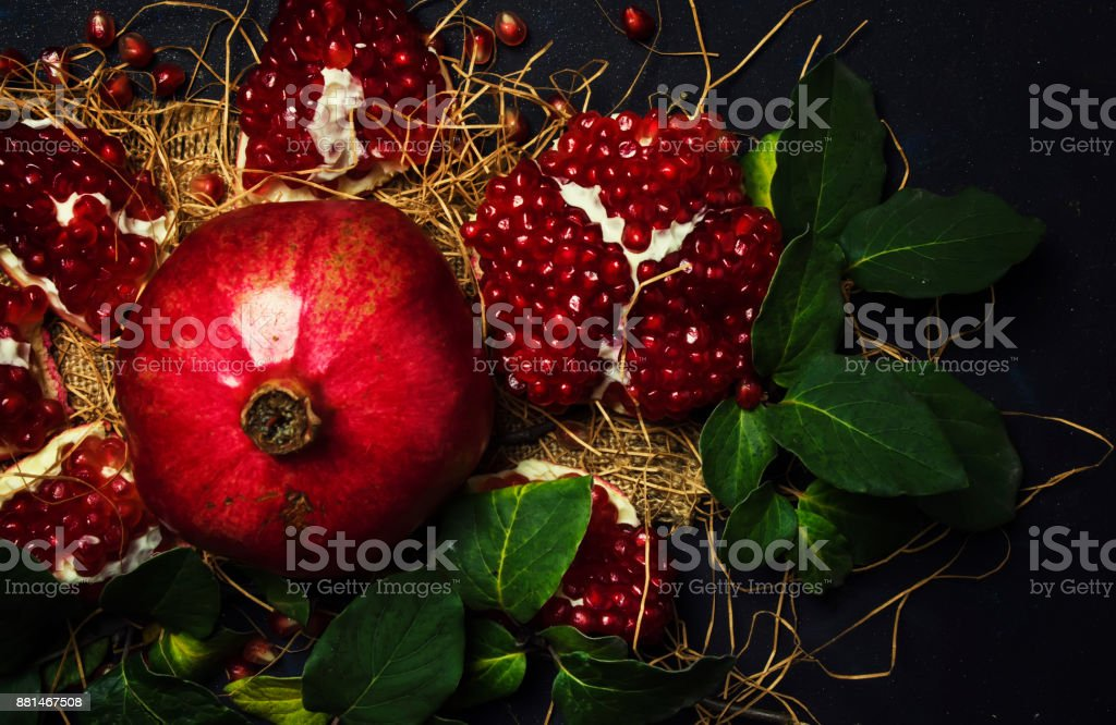Red Pomegranate In The Starw, Rustic Style, Black Background, Top View stock photo