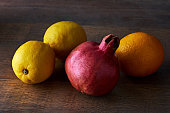 Red pomegranate, yellow lemon and an orange on a wood background