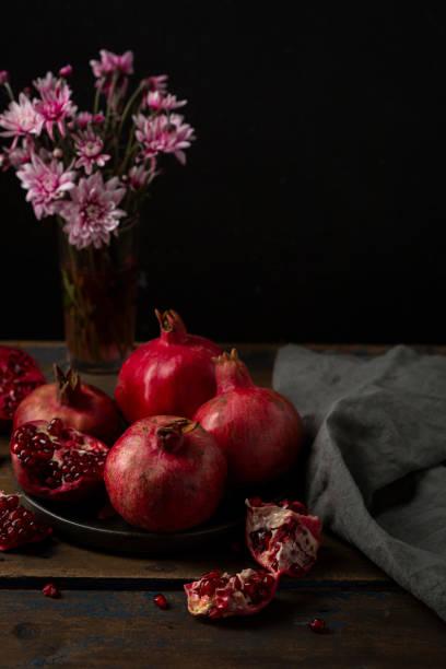 Red pomegranates on dark plate, food still life stock photo