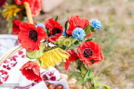 istock Red poppy flower wreath decoration on Eastern Orthodox easter passover holiday spring basket, Ukrainian fake flowers colors 1059738214