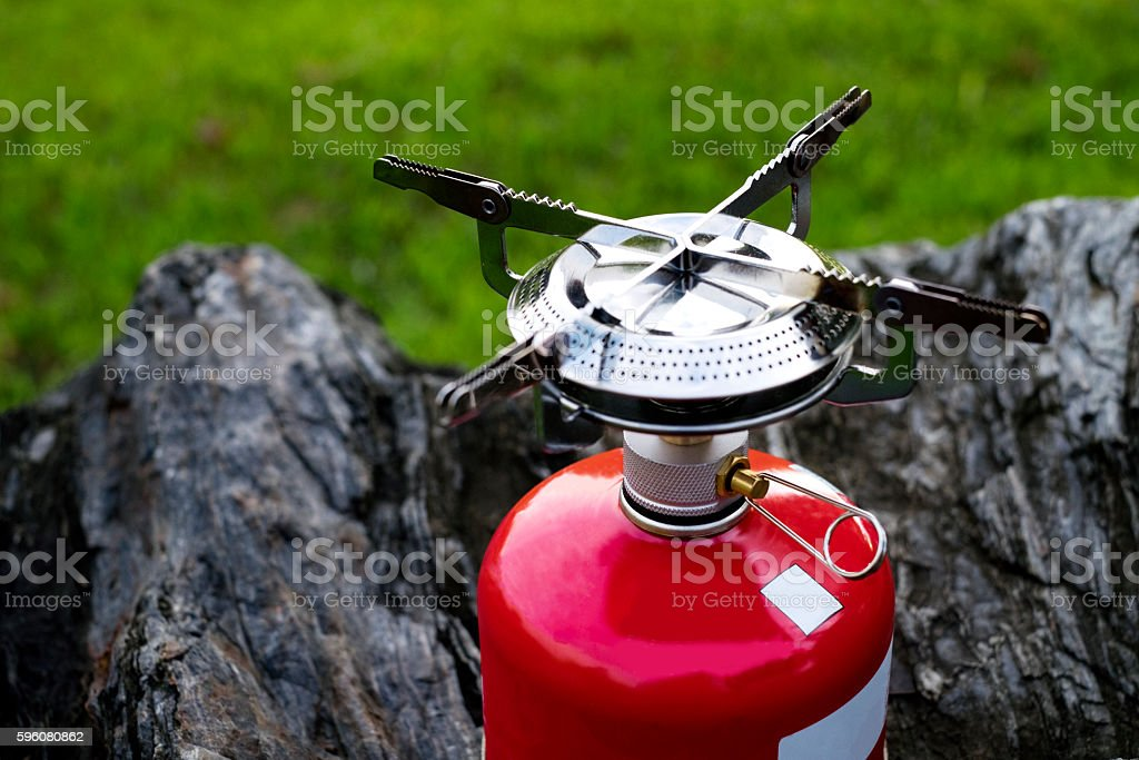 Red Portable gas Camping stove on a rock (Backpack Concept) stock photo