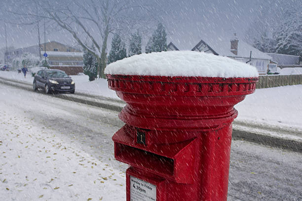 red post box in snow storm stock photo
