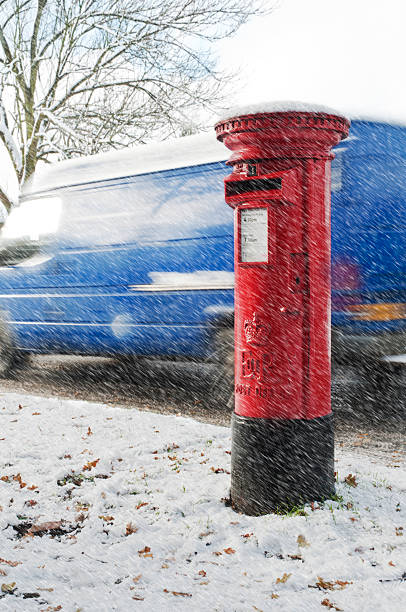 red post box in snow with moving blue van behind stock photo