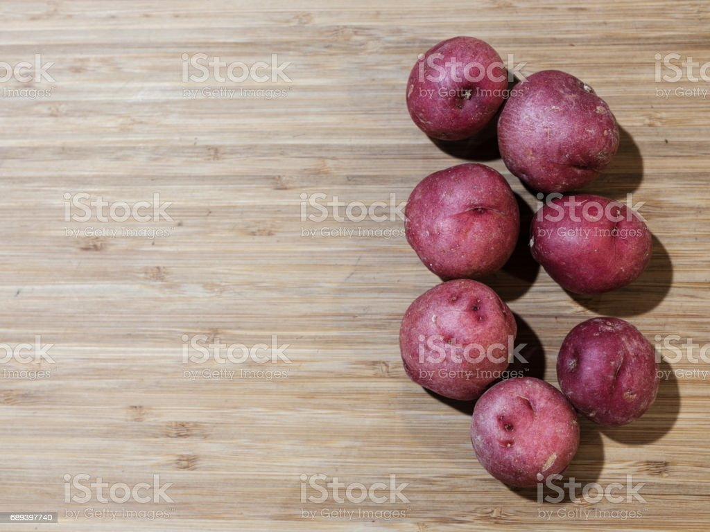 Red potatoes on cutting board stock photo