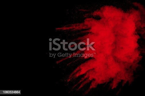 istock Red powder explosion on black background. Freeze motion of red dust particles splash on dark background. 1060534664