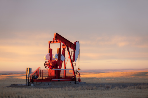 A pumpjack on the prairie. Alberta, Canada. This oil rig is located near Turner Valley, Alberta in an area where the oil industry is a major economic driver. Additional themes include crude oil, oil field, oilsands, prairie, rural, gas, fossil fuel, environment, energy, economy, rolling hills, scenic, southern alberta, red, agriculture, industry, equipment, and autumn.