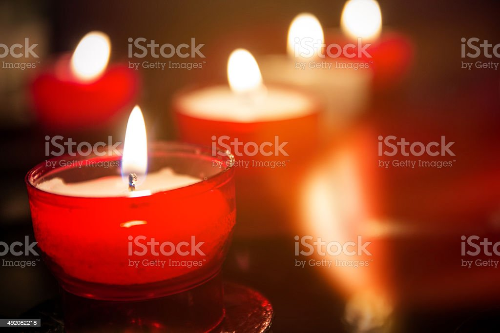 Red prayer candles in a row close-up in catholic church stock photo