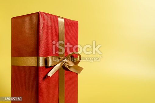 507751629 istock photo Red present close-up on yellow background 1189127162