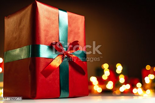 507751629 istock photo Red present on white table, defocused Christmas lights in background, bokeh 1189127063