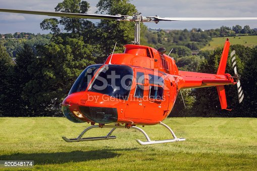A private helicopter takes off / lands on grass in a rural setting.