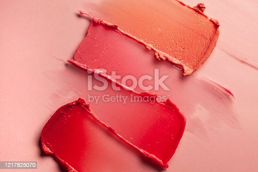 Smudged red purple pink textured tint or lipstick on multi-colored pink background