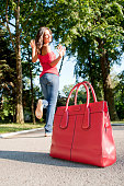 istock Red purse and young woman in the park 508327836
