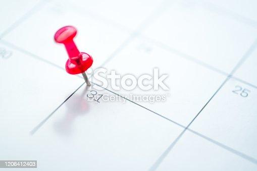 istock Red push pin on calendar 1206412403