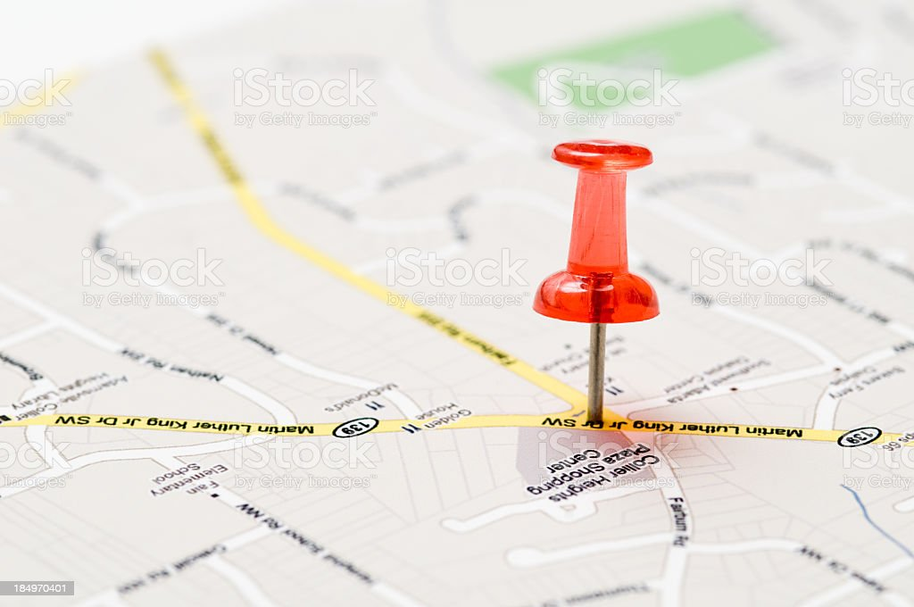 A red push pin stuck in a street map stock photo