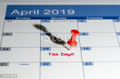 Tax day is April 15th for filing to IRS with red push pin in calendar for reminder