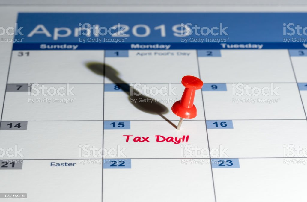 Red pushpin in calendar on April 15th for tax day stock photo